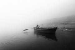 Indisches Mannsegeln auf dem Boot auf heiligem Fluss der Ganges am kalten nebeligen Wintermorgen Stockfotografie