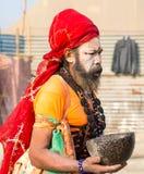 Indisches sadhu (heiliger Mann) geht in eine Straße während Festivals Kumbha Mela in Allahabad Lizenzfreies Stockfoto
