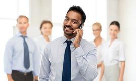 Indisk affärsman som kallar på smartphonen på kontoret royaltyfri foto