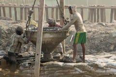Indisk arbetare som övervakar trava arbete som göras på platsen Royaltyfri Fotografi