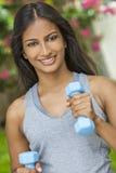 Indisk asiatisk flicka för ung kvinna som övar med vikter Arkivfoto