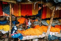 Indisk blommasäljare som sitter inom hans detaljhandel för att sälja ringblomman Galant på den Mullick Ghat blommamarknaden i mor arkivfoton