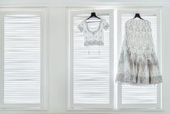 Indisk bröllopsklänning och blus som hänger på fönstren royaltyfri bild