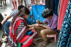 Indisk deg för manmålninghenna på kvinnas hand på den Russell marknaden i Bangalore Fotografering för Bildbyråer
