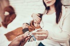 Indisk doktor som hemma ser patienter Doktorn tar temperatur av den gravida modern och dottern arkivbilder