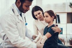 Indisk doktor som i regeringsställning ser patienter Doktorn använder förbinder på dotterns arm arkivbild