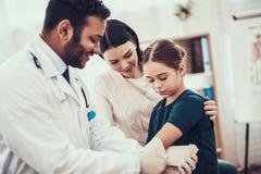 Indisk doktor som i regeringsställning ser patienter Doktorn använder selet på dotterns arm arkivfoton
