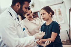 Indisk doktor som i regeringsställning ser patienter Doktorn gör injektionen i dotterns arm fotografering för bildbyråer