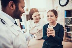 Indisk doktor som i regeringsställning ser patienter Doktorn ger poppillret och vatten till dottern royaltyfri fotografi