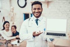 Indisk doktor som i regeringsställning ser patienter Doktorn poserar med bärbara datorn med modern och dottern i bakgrund arkivbilder