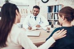 Indisk doktor som i regeringsställning ser patienter Doktorn tar anmärkningar som lyssnar för att fostra och dottern royaltyfri bild