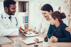 Indisk doktor som i regeringsställning ser patienter Doktorn visar minnestavlan för att fostra och dottern arkivfoto