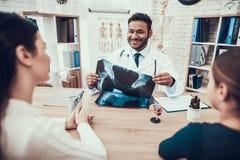Indisk doktor som i regeringsställning ser patienter Doktorn visar röntgenstrålen för att fostra och dottern arkivbilder