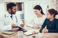 Indisk doktor som i regeringsställning ser patienter Doktorn visar skrivplattan för att fostra och dottern arkivfoton