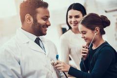 Indisk doktor som i regeringsställning ser patienter Dottern använder stetoskopet på doktor arkivfoto