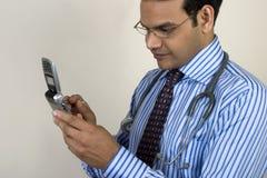 Indisk doktor som talar ett akut felanmälan Arkivfoto