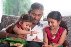 Indisk familj som använder minnestavladatoren Arkivbilder