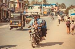 Indisk familj som kör på en motorcykel till och med gatan av staden Arkivbilder