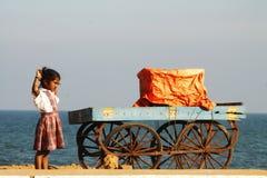 Indisk flicka med vagnen på stranden Royaltyfria Bilder