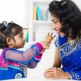 Indisk flicka som matar henne mumglass arkivbild