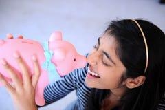 Indisk flickaholdingpiggybank Royaltyfria Bilder