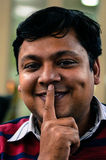 Indisk gladlynt man som gör ett uttryck för att hålla tystnad Royaltyfri Bild