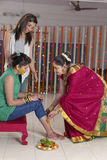 Indisk hinduisk brud med gurkmejadeg på framsida med systern och modern. arkivfoto