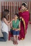 Indisk hinduisk brud med gurkmejadeg på framsida med systern och modern. royaltyfri foto