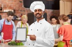 Indisk kock med minnestavladatoren på matlagninggrupp arkivfoton