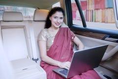 Indisk kvinna med bärbara datorn som ler i bil Arkivbilder