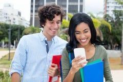 Indisk kvinna med den caucasian unga vuxna mannen och telefonen arkivfoto