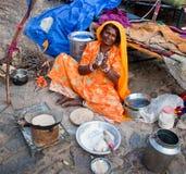 Indisk kvinna som förbereder ett mål på gatan, Jaipur, Indien. Royaltyfri Bild