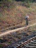 Indisk kvinna som går bredvid järnväg som balanserar påsen på hennes huvud Arkivbild