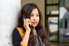 Indisk kvinna som lyssnar till en appell på hennes mobil Royaltyfria Bilder