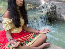 Indisk kvinna som mediterar i parkera Arkivbild