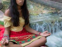 Indisk kvinna som mediterar i parkera Arkivbilder