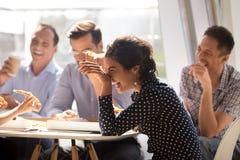 Indisk kvinna som skrattar äta pizza med olika coworkers i av arkivfoton