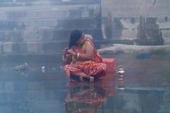 Indisk kvinna som tar det rituella badet i floden Ganges på den kalla dimmiga vintermorgonen varanasi Royaltyfri Foto