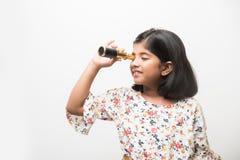 Indisk liten flicka som använder teleskopet och studerar utrymmevetenskap arkivbild