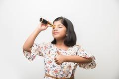 Indisk liten flicka som använder teleskopet och studerar utrymmevetenskap royaltyfria bilder