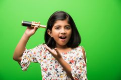 Indisk liten flicka som använder teleskopet och studerar utrymmevetenskap arkivfoton