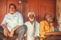 Indisk man för tre åldring som sitter den utomhus- förgångna trädörren av stadsmarknaden Royaltyfri Bild