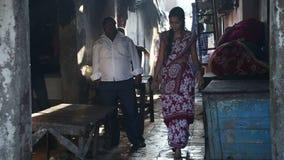 Indisk man och kvinna som går till och med en smal gata i Mumbai lager videofilmer