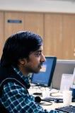 Indisk man som arbetar på kontoret med full koncentration Arkivbild