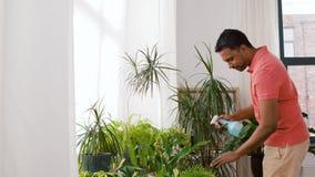 Indisk man som hemma besprutar houseplanten med vatten stock video
