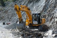 Indisk mangrävskopaoperatör, arbeten på vägkonstruktion Royaltyfri Bild