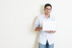 Indisk manlig användande bärbar dator för tillfällig affär Arkivbilder