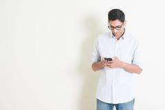 Indisk manlig användande smartphone för tillfällig affär Fotografering för Bildbyråer