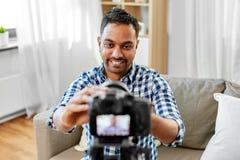 Indisk manlig video blogger som hemma justerar kameran royaltyfri foto