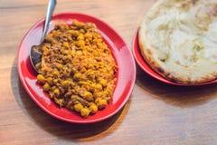 Indisk mat eller indisk curry i en kopparmässingsportionbunke med den nan bröd eller rotien royaltyfria bilder